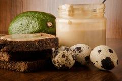 宏观三个鹌鹑蛋,有tahini的,黑麦面包,整个鲕梨瓶子 免版税图库摄影