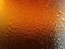 水宏观射击下降在深橙色颜色瓶的纹理,抽象背景的 库存图片