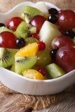宏观桔子、猕猴桃、的葡萄和的莓果沙拉  垂直 库存照片
