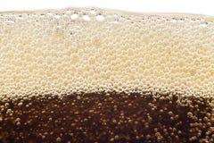 宏观泡影和泡沫在可乐玻璃墙上  免版税库存图片