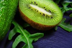 宏观绿色分类蔬菜和水果,鲕梨,猕猴桃,在页岩板,健康吃的概念的rucola沙拉,接近 库存图片
