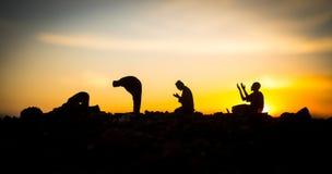 宗教回教的概念 祈祷在清真寺的背景的人剪影在日落 免版税图库摄影
