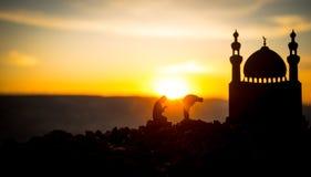 宗教回教的概念 祈祷在清真寺的背景的人剪影在日落 免版税库存图片