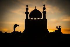 宗教回教的概念 祈祷在清真寺的背景的人剪影在日落 库存图片