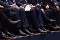 官员在候选会议地点坐 在长裤和黑鞋子的人的腿 文件和电话在手中 库存图片