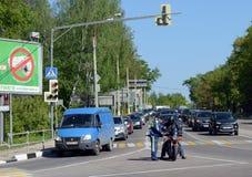 官员检查在城市街道上的警察摩托车骑士 免版税库存照片