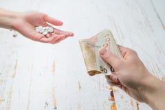 定价过高的药物概念-交换金钱的手为药物 医学或保险相关罪行概念 免版税库存图片