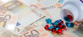 定价过高的药物概念-从容器的药片在monet票据 免版税图库摄影