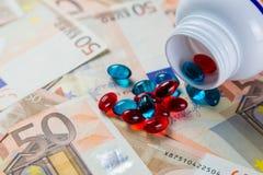 定价过高的药物概念-从容器的药片在monet票据 免版税库存图片