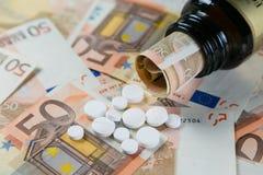 定价过高的药物概念-从容器的药片在monet票据 免版税库存照片