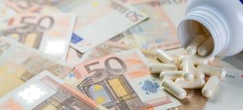 定价过高的药物概念-从容器的药片在monet票据 图库摄影