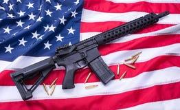 定制的AR-15马枪和子弹美国国旗表面,背景上 美丽的夫妇跳舞射击工作室妇女年轻人 免版税库存照片