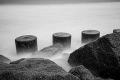 定向塔和岩石防波堤有具体防御块和海浪的 免版税图库摄影