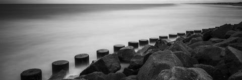 定向塔和岩石防波堤有具体防御块和海浪的 免版税库存图片