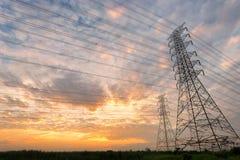 定向塔和输电线被射击反对日落 免版税库存照片