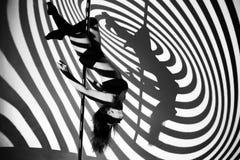 定向塔的女孩做锻炼反对黑酒吧的背景 免版税图库摄影