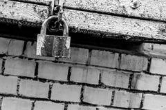 定调子在砖墙难看的东西基地背景特写镜头的灰色都市背景闭合的取决于的铁锁  免版税库存照片