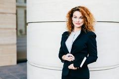 宜人卷曲妇女在手上正式地穿戴了,拿着笔记本,去有会议机智她的商务伙伴 Gorgeou 免版税库存图片