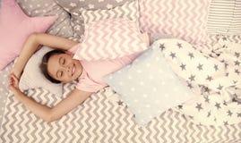 宜人唤醒 女孩微笑的愉快的孩子在与特征模式枕头和逗人喜爱的格子花呢披肩的床放置在她的卧室 图库摄影