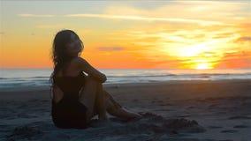 宜人地微笑通过观看的肉欲的妇女在海滩的美好的日落 股票录像