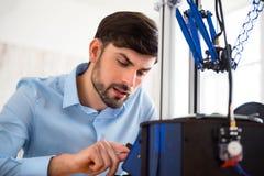 宜人的人与3d打印机一起使用 免版税库存照片