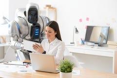 宜人的女孩和机器人使用片剂 库存照片