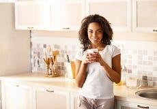宜人的女孩饮用的茶在厨房里 免版税库存照片