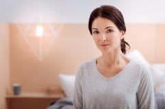 宜人的妇女在她舒适的卧室 免版税图库摄影