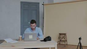 宜人的年轻摄影师饮用的咖啡在现代白天照相馆用专业设备 膝上型计算机和 股票视频