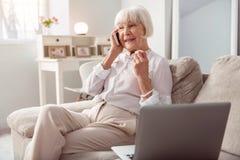 宜人的年长妇女愉快地谈话在电话 免版税库存照片