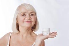 宜人的微笑的妇女有一个奶油色瓶在她的手 免版税库存照片