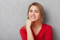 宜人的看起来的喜悦的女性有宜人的微笑,展示白色完善的牙,保留手在下巴下,是高兴是phot 库存图片