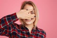 宜人的看起来的白肤金发的欧洲女性偷看照片通过手指,有暴牙的微笑,表示高兴,躲藏起来从面孔 库存图片