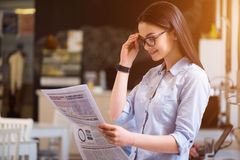 宜人的美丽的妇女读书报纸 免版税库存照片