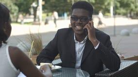 宜人的美国黑人的人有电话在与他的calleague的工休期间 免版税库存照片