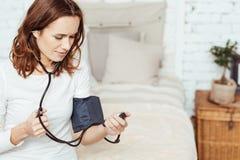 宜人的被集中的妇女测量的血压 图库摄影