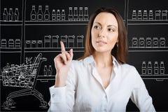 宜人的被集中的妇女购买在超级市场 免版税图库摄影