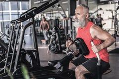 宜人的资深男性有密集的锻炼在运动中心 免版税库存图片