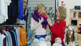 宜人的购物 两个女性朋友选择温暖的衣裳,试穿他们 股票录像