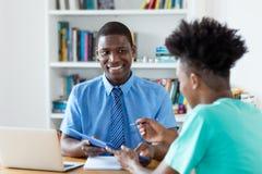 实习生和非裔美国人的buisnessman签署的合同 免版税库存图片