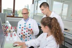 实习生在有原子模型的实验室 库存图片