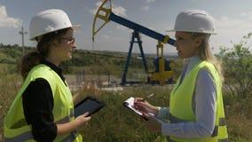 实习的学生技术员向她的行政经理工程学工作进展报告在钻油泵附近- 股票录像