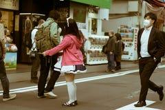 实施飞行物的日本佣人女孩对人在秋叶原,东京,日本 库存照片
