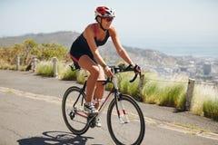 实践为三项全能竞争的妇女骑自行车者 库存照片