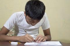 实践亚裔的男孩学会和得出3D在图画笔记本的形状 库存照片