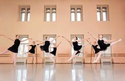 实践古典芭蕾的中等小组十几岁的女孩在一个大跳舞的演播室 免版税库存图片