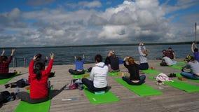实践在室外瑜伽的小组青年人分类 早晨瑜伽在木码头,湖背景行使 组 影视素材