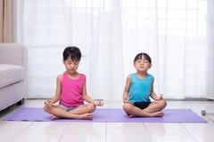 实践在席子的亚裔中国妹瑜伽姿势 库存照片
