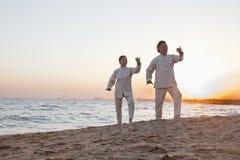 实践在海滩在日落,中国的两位老人太极拳 免版税库存照片