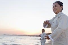 实践在海滩在日落,中国的两位老人太极拳 库存照片